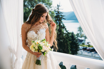 Portrait of beautiful young bride with cute smite in white wedding dress hold bouquet of flowers in her hands. Concept of clothes and family