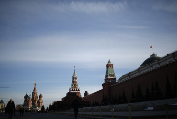 People walk along the Red Square, with St. Basil's Cathedral and the Mausoleum of Soviet state founder Lenin seen in the background, in Moscow