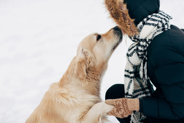 Image of dog giving paw to woman in black jacket on winter day