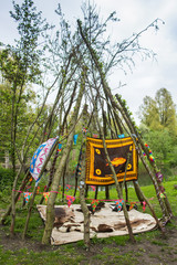 skins arranged below a tent of branches arranged in a wigwam shape viewed low angle outdoors in a clearing in a forest