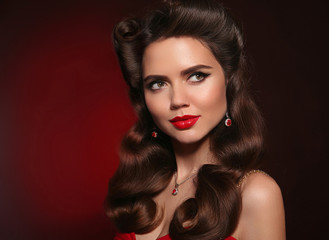 Pretty woman with red lips, retro wavy hair and expensive jewelry with diamond. Beautiful brunette girl with pinup curls hairstyle. Presenting your product. Expressive facial expressions.