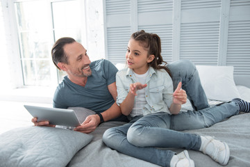 Pleasant interaction. Positive cheerful happy man holding a tablet and listening to his daughter while lying on the bed