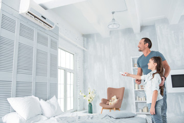 Climate control. Joyful positive nice girl standing together with her father and holding a remote control while turning on the air conditioner