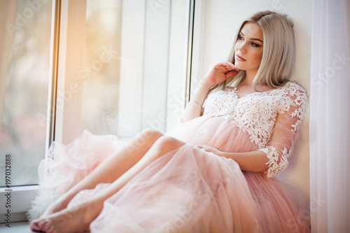 9a6cd9308 Beautiful pregnant young woman is wearing luxury pink lingerie dress at  home sitting on window sill