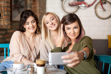 Female Friends In Cafe Taking Selfie Using Smart Phone. Women smiling, having fun, drinking coffee, laughing and enjoying their time.