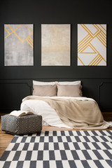 Paintings on black wall in bedroom