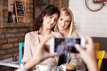 Girl friends in cafe posing for a photo. Three woman having a coffee together and having fun.