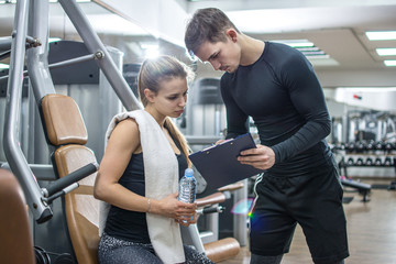 Personal trainer showing sports results to client in gym