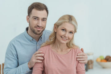portrait of grown son hugging smiling mother