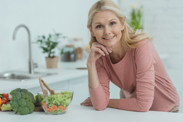 portrait of smiling mature woman with fresh salad on counter in kitchen