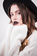 Close up portrait of a fashionable glamorous woman with dark lips in a hat and a white sweater. A beautiful girl with a bright makeup looks at the camera, hands on her chin