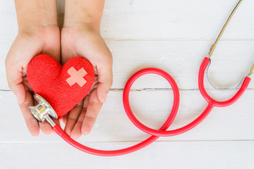World health day, Healthcare and medical concept. Woman hand holding red heart with Stethoscope, notepad or notebook, thermometer and yellow Pill on Pastel white and blue wooden table background .