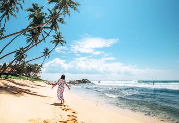 Woman in long dress walks on tropical island beach