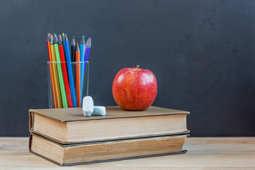 Back to school supplies. Books, apple, chalk, pencils on wooden table. School blackboard background