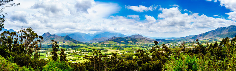 Panorama view of the Franschhoek Valley in the Western Cape of South Africa with its many vineyards in the Cape Winelands, surrounded by the Drakenstein mountain range, as seen from Franschhoek Pass
