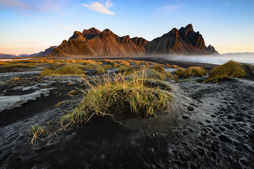 black sand and grassy mounds with morning dawn at Stokksnes, Iceland with the mountain Vestrahorn in the background