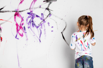 Little girl painting a white wall with colorful paint.