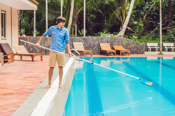 Cleaner of the swimming pool . Man in a blue shirt with cleaning equipment for swimming pools, sunny
