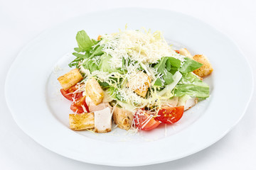Delicious caesar salad. Caesar salad with cheese, chicken, tomatoes, rusks and green leaves of arugula.