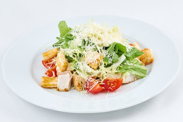 Delicious fresh caesar salad. Caesar salad with cheese, chicken, tomatoes, rusks and green leaves of arugula.