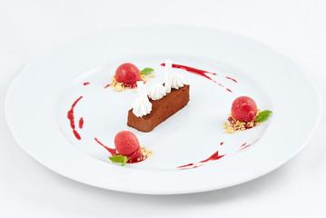 Delicious dessert. Fresh chocolate cake with berry ice cream balls.