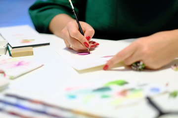A woman draws a colored pencil on paper in an art studio
