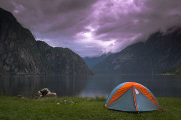 View of a camp tent by a lake against cloudy sky