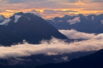 Scenic view of snowcapped mountain range in clouds