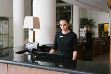 Pretty hotel worker working in reception