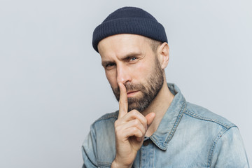 Portrait of serious bearded male with attractive look, keeps fore finger on lips, looks with secret expression, asks to keep silence and not tell his secret to anybody, isolated over grey background