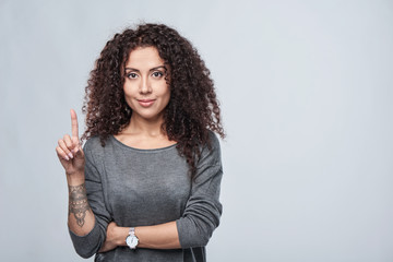 Hand counting - one finger. Curly woman pointing up at blank copy space Wall mural