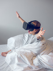 Cute boy playing with VR glasses