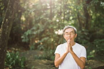 Pray of senior Asian man in nature park