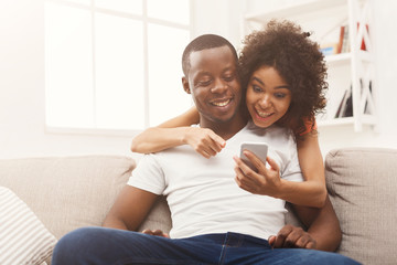 Black couple making using smartphone at home