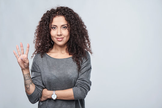 Hand counting - four fingers. Smiling woman showing four fingers
