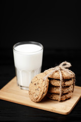 Tasty cookies and glass of milk on rustic black wooden background.