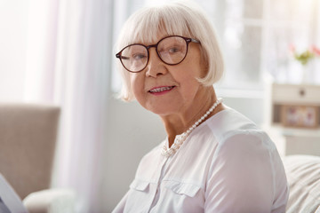 Great mood. The close up of a pleasant joyful senior lady in eyeglasses smiling at the camera while sitting on the couch