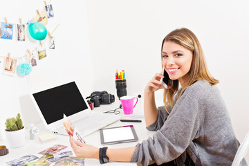 Cheerful female photographer in her home office working. Young freelance artist working from home