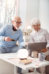 We love shopping. Upbeat elderly man and his wife choosing an item in the online shop, pointing at it on the laptop screen, while the man giving his bank card to make a payment