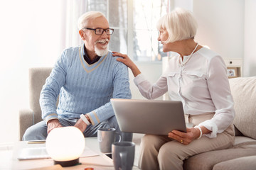 Good news. Joyful senior woman holding a laptop and laughing together with her husband while discussing the recent news, having read them online