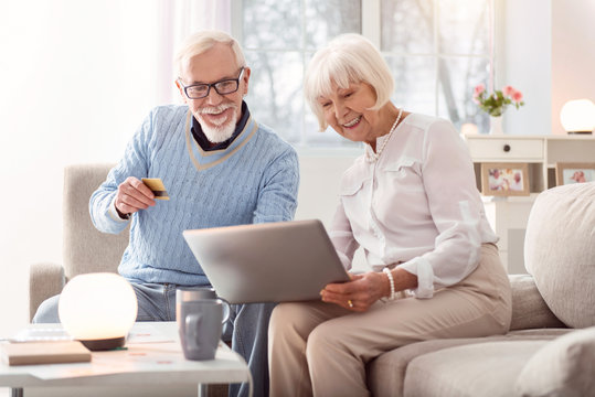 Fast payment. Cheerful senior man handing his credit card to his wife while they looking through an online shop and buying something