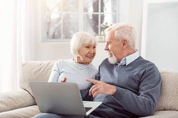 Sharing opinions. Joyful senior husband and wife sitting on the sofa in the living room and discussing an article together, having read it online