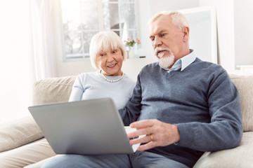 Keeping themselves updated. Pleasant elderly husband and wife sitting on the couch and scrolling the newsfeed on the laptop, being slightly dissatisfied with the news