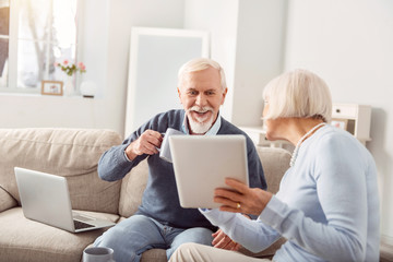 Check it out. Pleasant elderly woman showing her husband a tablet with an open news article on it, and the man checking it out and drinking coffee