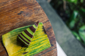 Raw mint chocolate spiral mousse cake on a leaf. Gluten-free, wheat-free, dairy-free, sugar-free dessert. Copyspace, top view