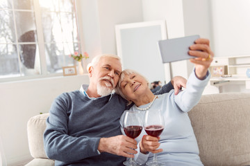 Capturing happy moment. Joyful senior husband and wife cuddling on the couch and taking a selfie while drinking wine