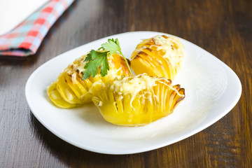 Fototapete - hasselback potatoes with yellow cheese