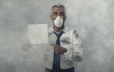 Man with pollution mask holding a sign