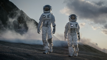 Two Astronauts in Space Suits Confidently Walking on Alien Planet, Exploration of the the Planet's Surface. In the Background Research Base/ Station and Rover. Space Travel, Colonization Concept. Fototapete