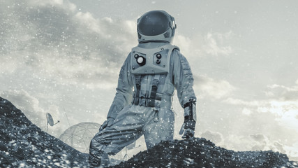 Astronaut Looking Around while Standing on the Hill During Blizzard on Frozen Alien Planet. In the Background His Base/ Research Station. Colonization, Technological Advance Brings Space Exploration.